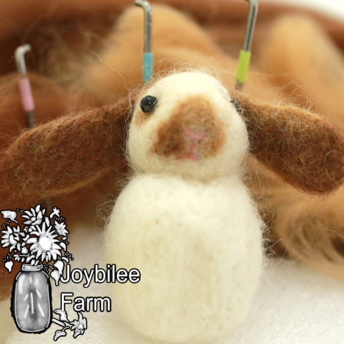 needle felted 3d rabbit with wool and needle felting needles in background