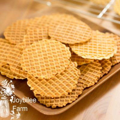 finished pizzelles on a brown serving tray