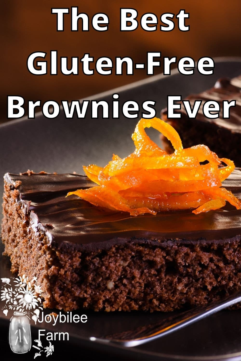 Brownies, topped with chocolate and candied orange peel on a grey tray.