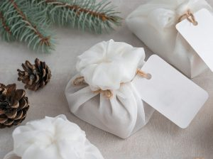 Christmas presents wrapped with white furoshiki fabric
