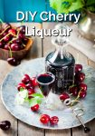 Cherry liqueur in a decanter and glass beside fresh cherries.