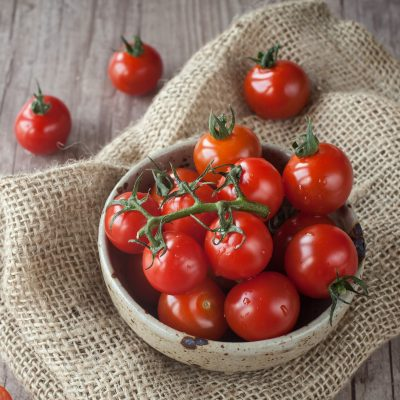 Fresh cherry tomatoes in a bowl on folded burlap