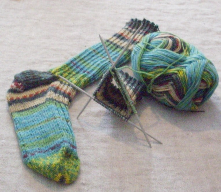 One completed knitted sock, a ball of yarn and a yarn on three needles.