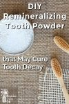 Tooth powder in a container by a couple bamboo toothbrushes