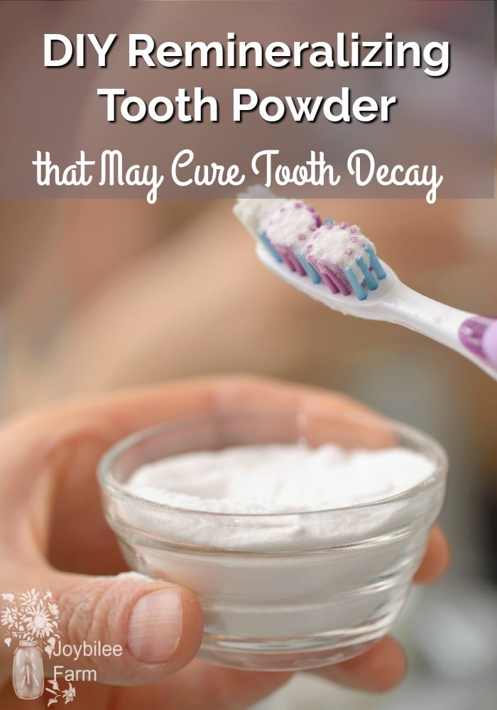 Hand holding tooth powder and tooth brush