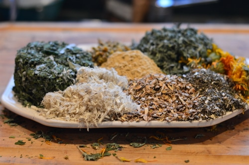 dried herbs on white plate sitting on a table
