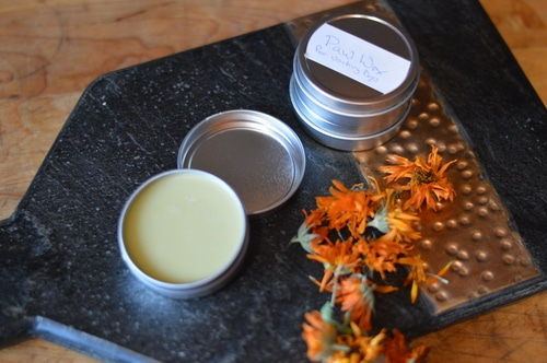 Dried calendula flowers and salve on a cutting board