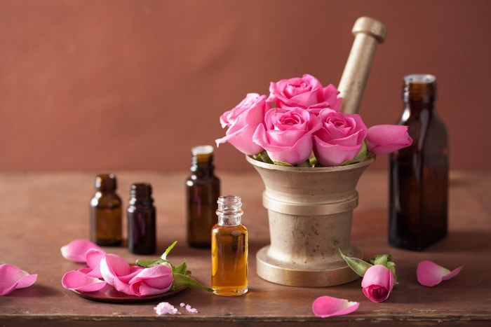 Pink roses in a mortar and pestle. Rose petals scattered around and apothecary bottles on a table