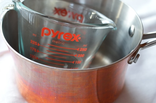 Stock pot with a glass measuring cup inside
