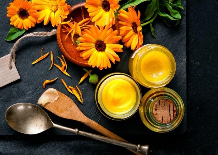 Fresh calendula flowers by glass jars full of yellow salve