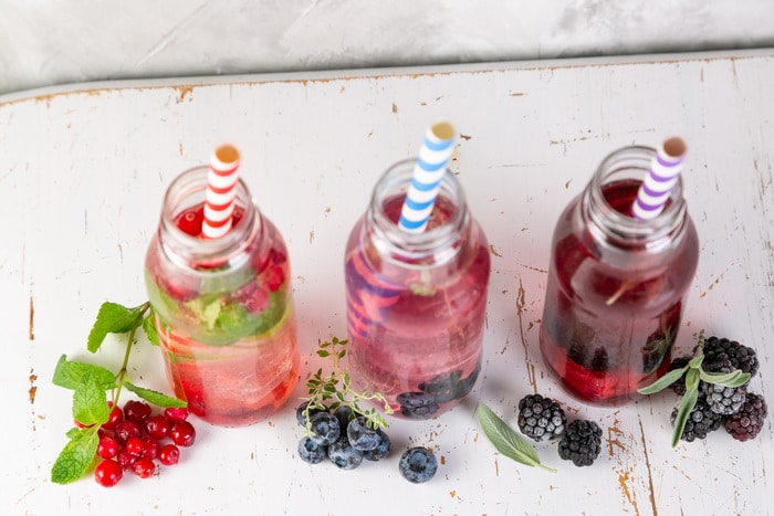 drinking vinegar in glass bottles with colorful straws