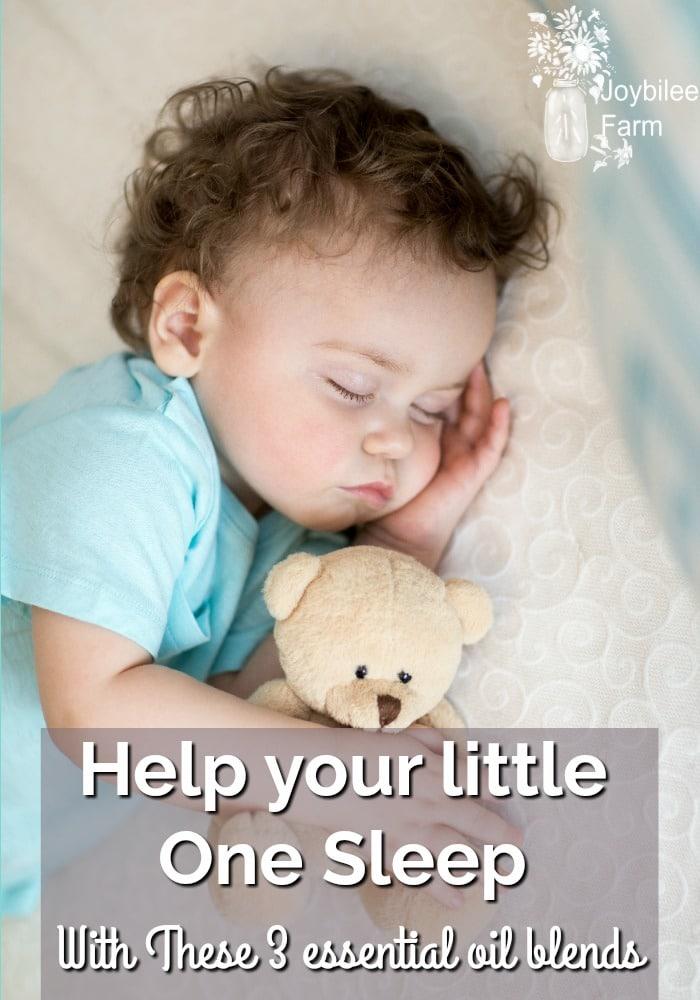 Sleeping baby cuddling a teddy bear