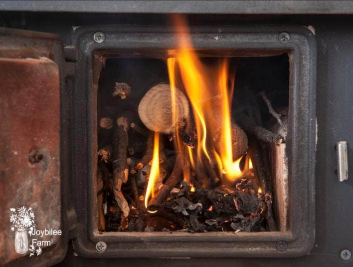 open woodstove door with wood ash uses