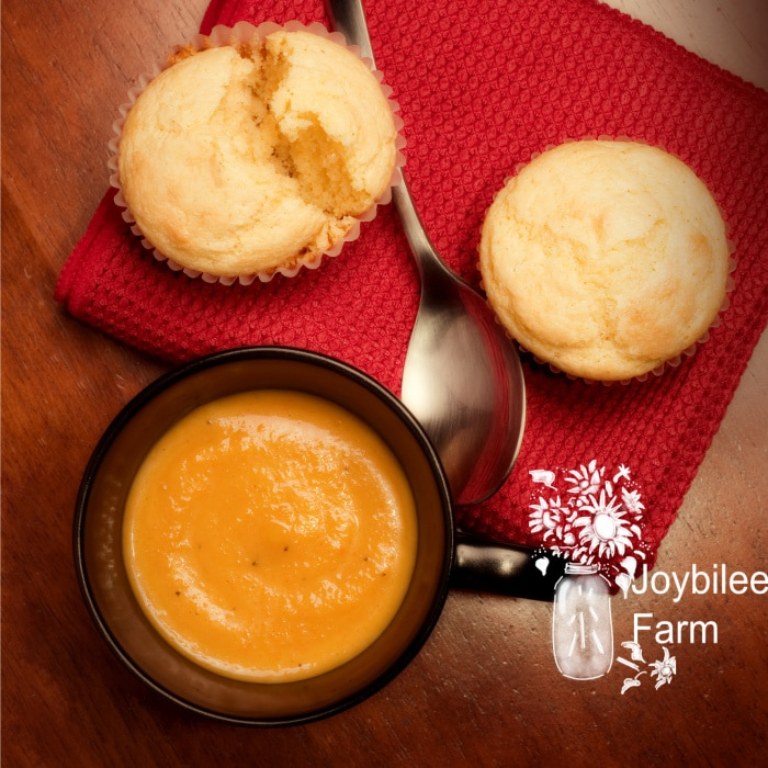 A mug full of creamy butternut squash bisque with corn muffins on a wooden table.