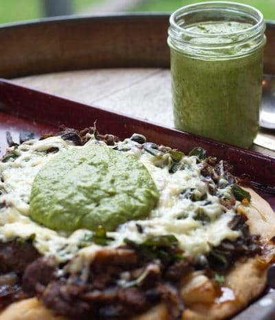 asparagus pesto in a jar, and on pizza in the foreground.