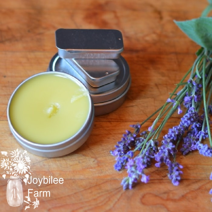 prepared salve on a wooden table with fresh lavender beside it, salve is a great way to apply essential oils for congestion